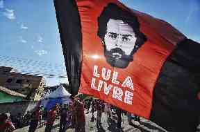 "A supporter holds a flag that reads ""Free Lula,"" in front of the Federal Police Department"