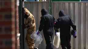 Investigators in chemical suits works behind screens erected in Rollestone Street, Salisbury