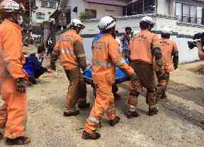 Emergency rescue teams recover the body of a flood victim in Hiroshima,