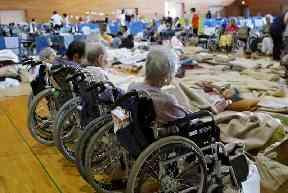 Elderly people from a nursing home take shelter following heavy rain, in Soja, Okayama prefecture