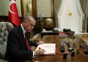 Turkey's President Recep Tayyip Erdogan signs the decree for his new cabinet