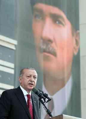 Turkey's President Recep Tayyip Erdogan, backdropped by a poster of modern Turkey founder Mustafa Kemal Ataturk