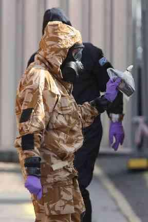 Investigators in chemical suits work behind screens erected in Rollestone Street, Salisbury