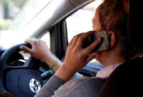 Driving while using mobile phones