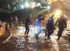 Rescuers hold an evacuated boy inside the Tham Luang Nang Non cave