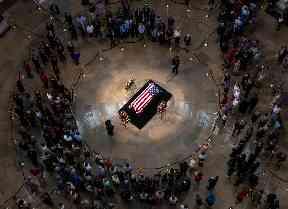 Tributes: Members of the public walk past the flag-draped coffin of John McCain.