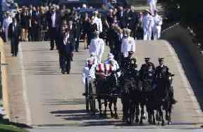 Family members, including Cindy McCain, follow the horse-drawn carriage