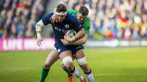 Ryan Wilson is tackled by Ireland's Johnny Sexton.