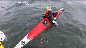 A man was struggling to get back into his kayak.