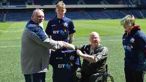 Scottish Rugby kit manager John Pennycuick presents wheelchair team coach Adam Mould with official playing kit.