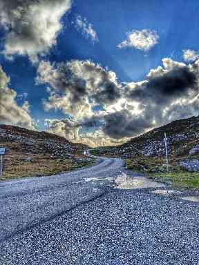 Striking clouds rumble over a winding road.