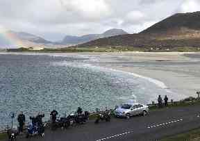 Bikers stop for a rest near the white sandy beach.