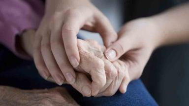 Elderly woman holding hands with young person. Care home, caring picture from iStockphoto