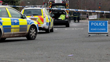 Road accident with police tape, two police cars and road closed sign in foreground.