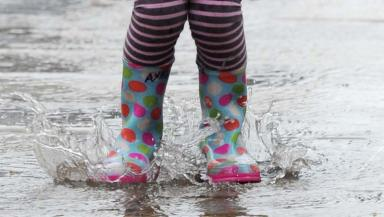 Little girl's feet in puddle.