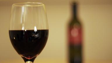 Wine glass and unidentifiable bottle quality image. From Flickr Creative Commons
