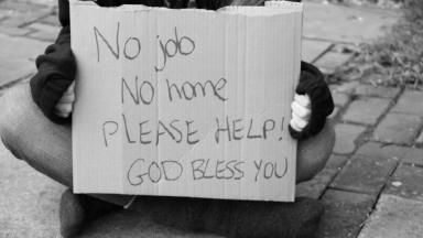 Homeless man with sign on street in black and white generic