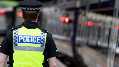 Quality generic image of a British Transport Police officer next to train.