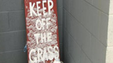 Snow sign saying 'Keep off the Grass'