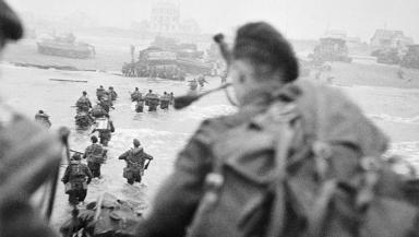 D-Day landings. Brigade commander Lord Lovat DSO MC, can be seen striding through the water to the right of the column of men. The figure nearest the camera is the brigade's bagpiper, Piper Bill Millin.
