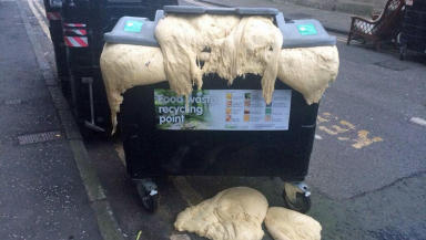 Pizza dough coming out of recycling bin on Leith Walk, Edinburgh.