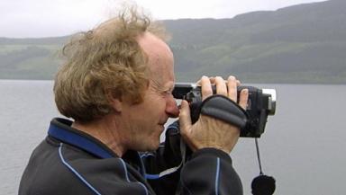 Loch Ness Monster hunter with camera at Loch Ness