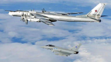 Intercepted: RAF Typhoon flying alongside larger Russian Bear bomber.