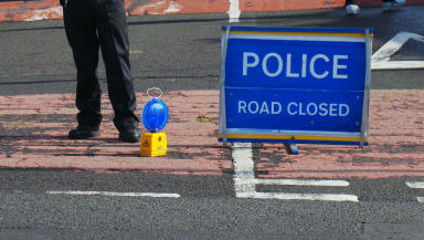 Police road closed sign and police officer legs. Generic shot for road accident, road crash, road collision, crash, smash #crashgeneric