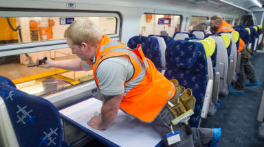 ScotRail worker inside new look train. Workers putting final touches to first train in August 2015. PR image Quality news image uploaded September 1 2015