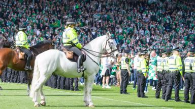 Disorder: Police on the pitch at Hampden on Saturday.
