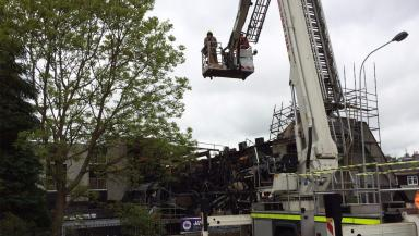 Damping down: Firefighters remained on scene on Friday.