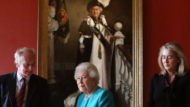 The Queen stands in front of the new portrait produced to mark her 90th birthday year.