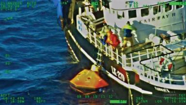 Rescue: Fishermen pulled from liferaft by crew of Fairway II.
