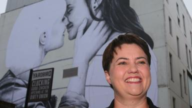 Mural: The Conservative leader posed for pictures beside a mural of a lesbian couple kissing.