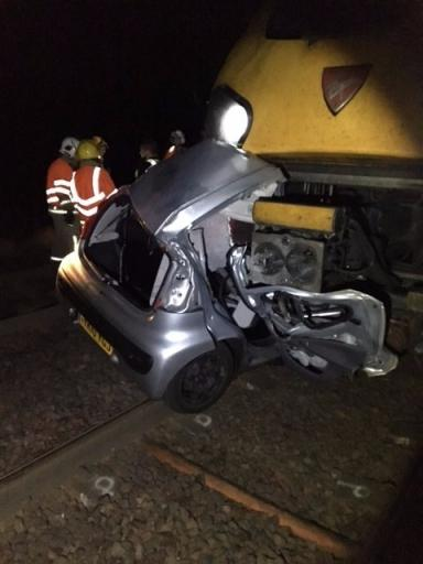Level crossing: Car lodged underneath train.
