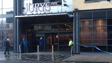 Murder bid: Police stand guard outside Glasgow hotel after man hit by car.