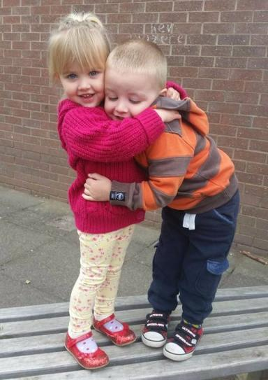 Cuddles: Three-year-old twins are inseparable when together.