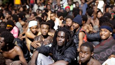 Migrants sit on the ground after storming a fence to enter Ceuta.