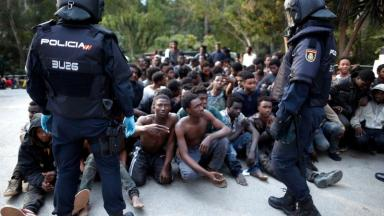 Migrants sit on the ground next to Spanish police officers after storming a fence to enter Ceuta.