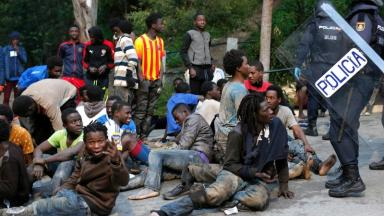 Migrants sit on the ground after storming a fence to enter the Spanish enclave of Ceuta.