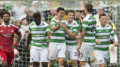 Tom Rogic (centre) celebrates his free kick.