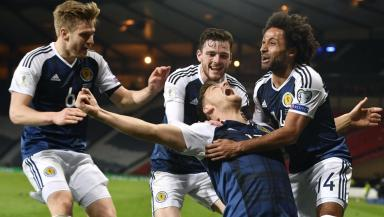 Chris Martin celebrates his 88th minute winner against Slovenia with his team mates.
