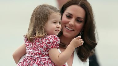 Princess Charlotte is carried by her mother as they arrive in Poland.