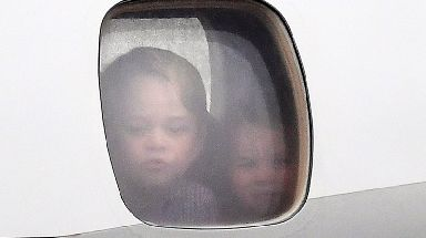 The young royals look out of the plane window.