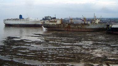 Beached: Empress of Britain, far left, scrapped in Alang, India.