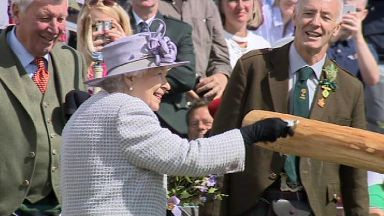 Aboyne: Queen dedicates caber with a dram.