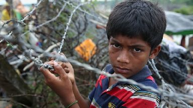 A Rohingya boy waits at the border.