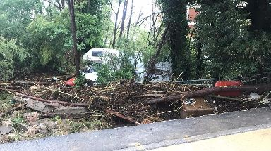 A camper van lies by the side of a road following floods in Leghorn.