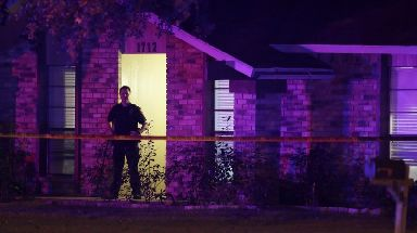 A police officer stands guard outside the house where the mass shooting took place