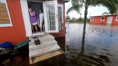 A Florida family looks on as their home is surrounded by flood water.